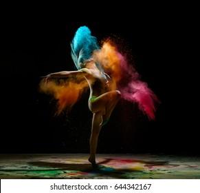 Girl dancing in a cloud of color dust studio portrait