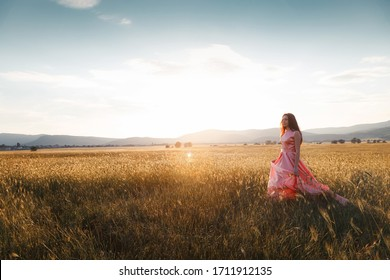 girl dancing in a field in a beautiful pink dress at sunset. ideal for advertising and photo sun shines bright and juicy
