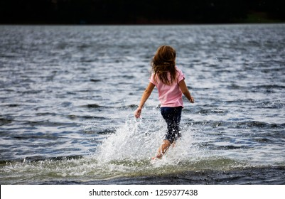 Girl dancing in flooded water on dock left foot forward