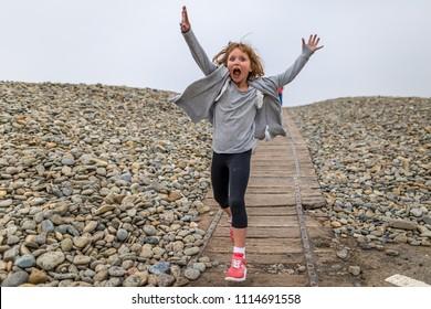 Girl dancing floss on seaside in Pembrokeshire, Wales