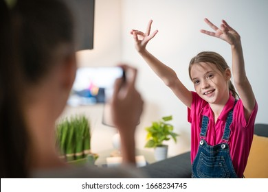 Girl dancing and making fun pose while sister films her or take pictures with a smartphone. Concept for technology use, artistic expression among young people. Girl doing a victory sign with fingers.