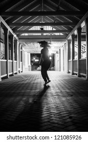 Girl dancing at night on a covered bridge, her hair flying. B&W image