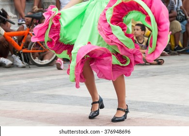 girl dancing old dances with green and orange dress with child in the skirt - Havana, Cuba