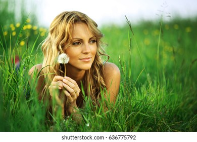 girl with dandelion on green field