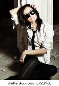 The girl in dark glasses at a column