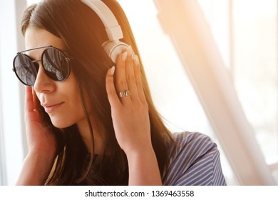 A girl with dark hair in headphones listening to music, sitting in a room, airport, office. A young woman with glasses and a light shirt. Close up.