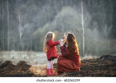 girl the daughter and mother in a red coat skirt the field on the grass in the forest at sunset
