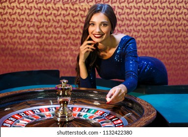 Girl dealer spin the spinner. Dealer in the casino behind the roulette table