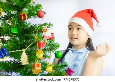 Girl decorates Christmas tree for new year celebration