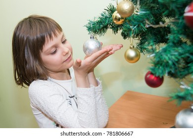 The girl decorates the New Year's tree