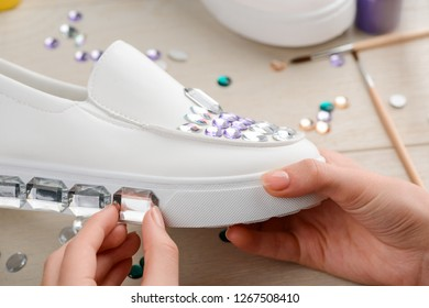 Girl decorates outsole of shoe with rhinestones, close up shot. Customizing simple shoes and giving them fashionable look.