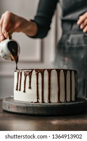 girl decorating a white cake with chocolate