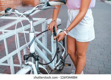 The girl defends her bike in park in summer. Removes from the parking lot, uses a protective chain, sets the password, the cipher to the lock against theft of bicycle.