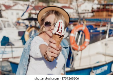 girl with delicious ice cream stands on the pier near the yachts - image
