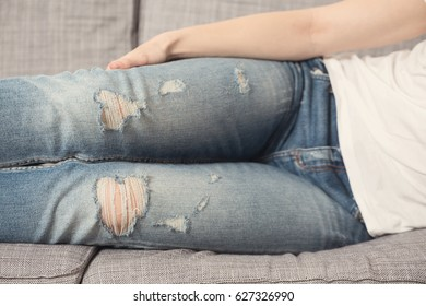 Girl with denim fabric pants, sitting on the sofa; denim torn on the knees and threads coming apart