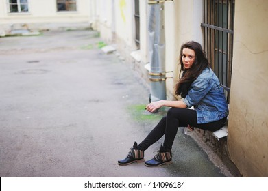 girl in a denim jacket and boots sitting in the courtyards in the inner city