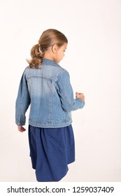 The girl in the denim jacket, stands back.