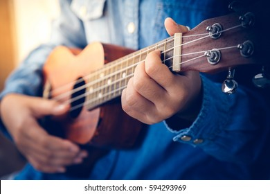 A girl in denim shirt playing ukulele in close up view, sunset, selective focus,  vintage tone.