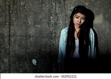 Girl in depression , grief , despair, discouragement , despair , a concrete wall background lighting was dim .