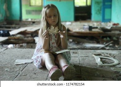 The girl in the destroyed schoolhouse are sitting on the floor.
