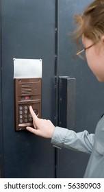 a girl dials digits on an entrance door intercom