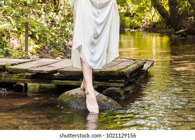 girl dipping her foot in the water