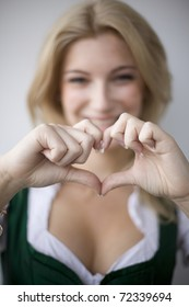 Girl in a dirndl shape with her hands a heart