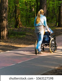 girl and disabled person walks along green park