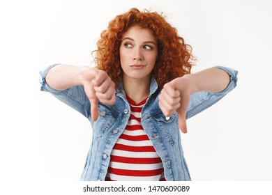 Girl disappointed bad movie. Reluctant redhead curly-haired female look away bored show thumbs down displeased express dislike disapproval thinking game awful, standing white background