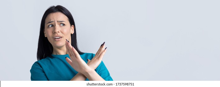 Girl disapproving with no crossing hands sign make negation gesture. Portrait of pretty woman on grey background