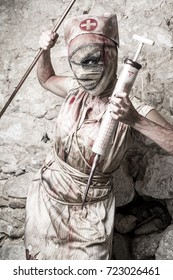 Girl disguised as a zombie nurse with a huge syringe, vertical image.
