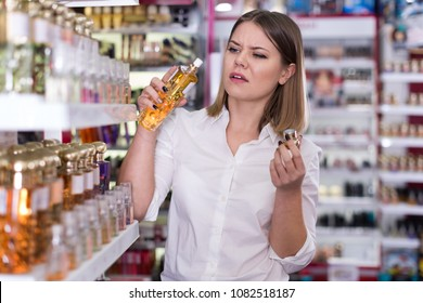 Girl with displeasure sniffing unpleasant smell of perfume in the beauty store