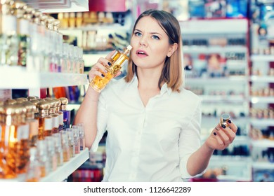 Girl with displeasure sniffing unpleasant smell of perfume in beauty store