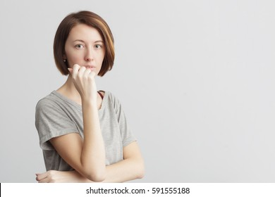 Girl with distrust and doubt looks forward, her arms near face