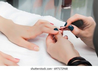 Girl do a manicure and paint nails with red lacquer in the beauty salon