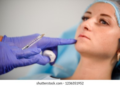 girl do plastic operation in medical clinic; doctor does lip augmentation surgery; injecting operation on lips