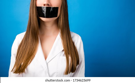Girl doctor in a white coat with black tape over her mouth on a blue background, silence and non-disclosure of medical secrets