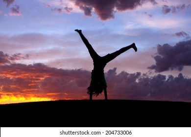 A girl does a cartwheel at sunset on the Rathdrum Prairie in north Idaho.