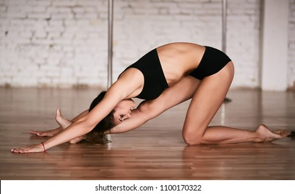 Girl does stretching of her back and legs before a training in the pole dance gym