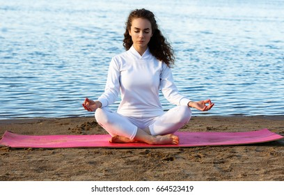Girl does yoga on the beach. Model. White suit. White clothing. Sand. Water. Sunset