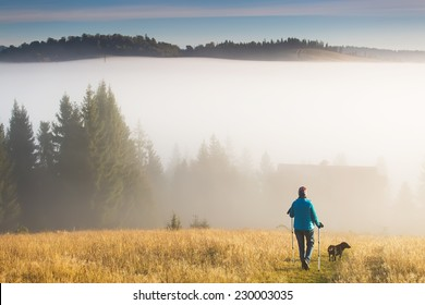 Girl with a dog goes towards the house standing on a mountain with Trekking pole in the morning fog. Landscape composition, background mountains and sunrise.