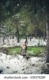 Girl with dog on background of a winter fores