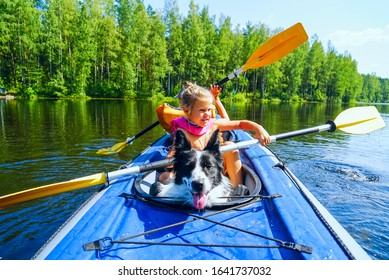 A girl with a dog sitting in a kayak on the lake