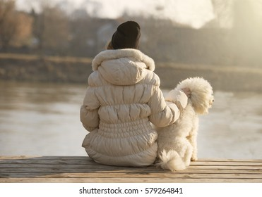 Girl and a dog sitting on a bench by the river