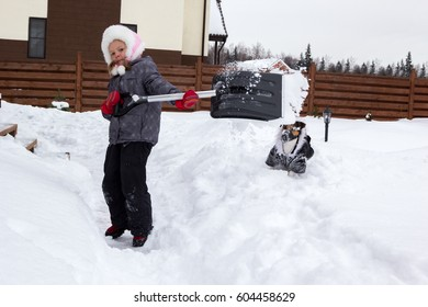 Girl with a dog takes the snow off the track with a shovel