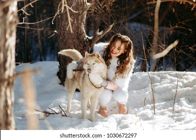 girl with a dog in the winter forest