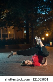 Girl doing a breakdance move at night on brick floor, wearing a red t-shirt