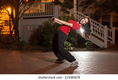 Girl doing a breakdance move at night on brick floor in urban setting, wearing a red t-shirt