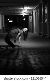 Girl doing a breakdance move at night on brick floor. B&W image