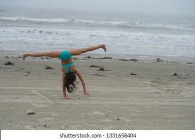 Girl doing a cartwheel along the beach near Galveston, TX